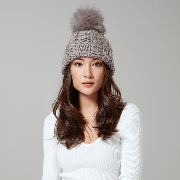 Dieser reizende Hut kennzeichnet ein einfaches Kabelmuster und wird mit einem Bommel beendet. Es wurde von Quail Studio entworfen und in einem Farbton aus Big Wool, einem Garn aus 100% Wolle, gestrickt.